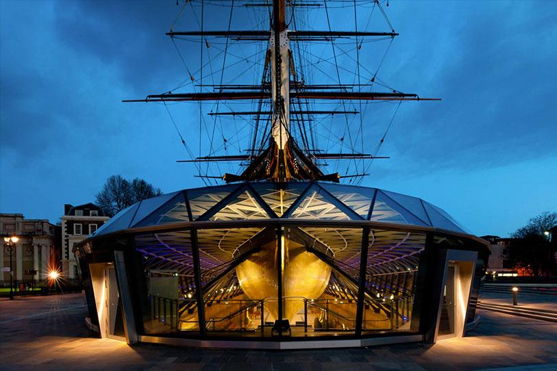 Cutty Sark shown at night with the visitor centre directly in front of it