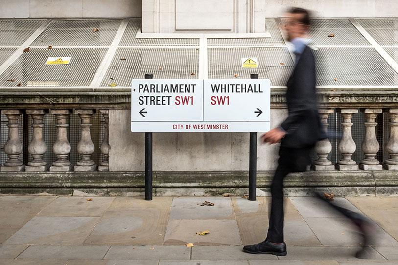 Street sign showing Parliament Street and Whitehall with a man walking past who is blurry